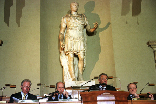 A statue of Roman emperor Julius Caesar lurks above EU foreign ministers and officials during a news..