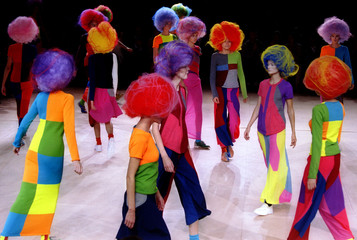 Models for Comme des Garcons parade on stage with large geometric multi-coloured ankle-length skirts..