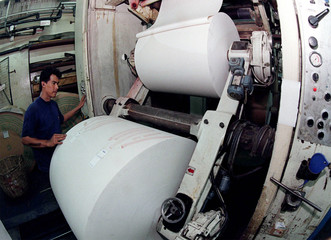 A newspaper engineer loads a roll of newsprint into the printing machine in Kuala Lumpur March 11. A..