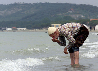 AN OLD ETHNIC ALBANIAN FROM KOSOVO WASHES HIS FACE WITH SEA WATER.