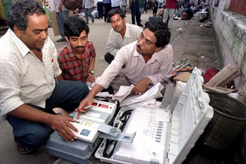 INDIAN POLLING OFFICIALS PREPARE AN ELECTRONIC VOTE-MACHINE IN CALCUTTA.