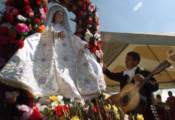 A YOUNG MEXICAN MARIACHI PLACES A FLOWER AT THE ICON OF CECILIA, THE PATRON SAINT OF MARIACHI MUSICIANS.