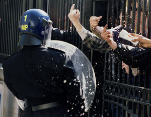 A London riot policeman is showered by beer and abuse as he tries to keep environmental protesters f..