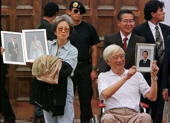 Japanese ambassador Morihisha Aoki holds up a portrait of Japanese Prime Minister Ryutaro Hashimoto ..