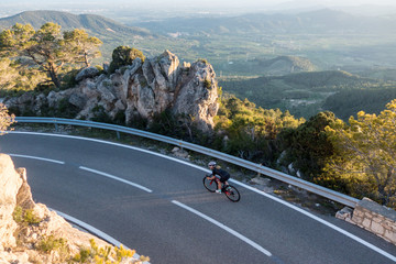 Young female cyclist riding, cycling on sunset ray glissened road high in the spainish mountians narrow road surrounded by green trees and huge sand colored rocks.