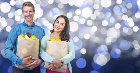 Happy couple carrying fruits in paper bag over bokeh