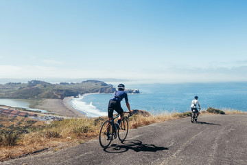 Group of cyclists, teammates, friends, descending windy narrow road next to the bay with fog and water and blue skys san francisco in norhtern california.
