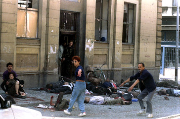 Dead and wounded people lie outside Sarajevo city indoor market after a mortar shell exploded at the..