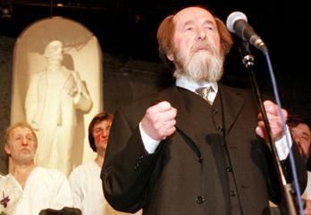 RUSSIAN WRITER ALEXANDER SOLZHENITSYN STANDS UNDER THE STATUE OF THE BOLKSHEVIK LEADER VLADIMIR LENIN.