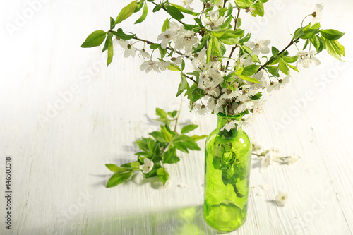 Branches Of Blooming Tree Flowers And Leaves In Glass Vase On Wooden