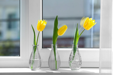 Glass vases with beautiful tulips on windowsill