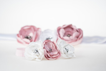 Gentle hand-made bow for a baby girl, with a matching mommy's head-band in background, cute fashion accessories for weddings and special occasions