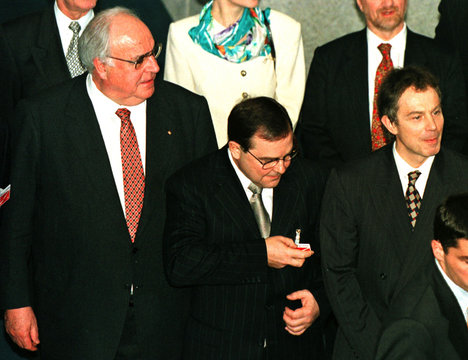 Estonia's Prime Minister Mart Siiman checks his ID badge (C) as he stands between Germany's Chancell..