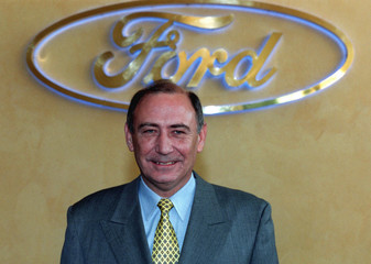 Ford manager James D. Donaldson, 54, of Scotland poses in front of a company logo of car manufacture..