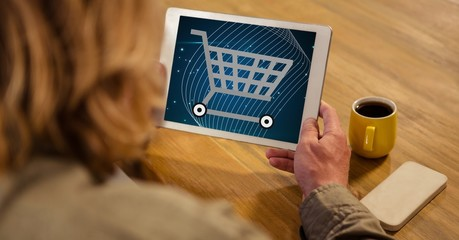 Woman looking at shopping cart icon on tablet PC