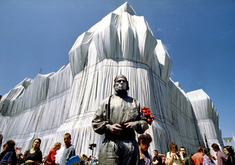 A silver dressed and painted street artist performs when thousands of visitors watch the German Reic..