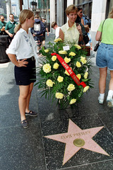 Tourists pose for pictures next to a spray of flowers placed at Elvis Presley's star on the Hollywoo..