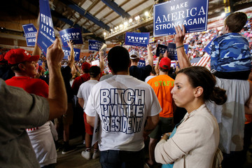 """A man with a """"Bitch I'm The President"""" shirt listens to a speaker before a U.S. President Donald Trump rally in Harrisburg"""