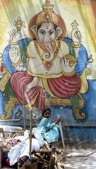 A little girl sits beneath a picture of the elephant -headed Hindu God Ganesh while her father sleep..