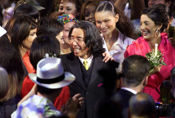 Japanese designer Kenzo Takada is congratulated by models after his Spring/Summer 2000 ready-to-wear..