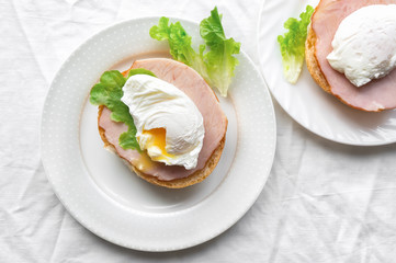 Two poached egg on a bread with salad and beef meat. Top view photo. Healthy breakfast.