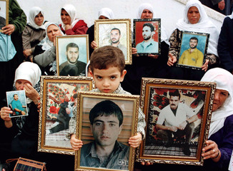 Relatives of jailed Palestinians hold up portraits of their family members during a rally November 2..