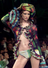 A MODEL FOR FRENCH DESIGNER JEAN-PAUL GAULTIER PRESENTS COLOURFUL PIRATE BLOUSE.