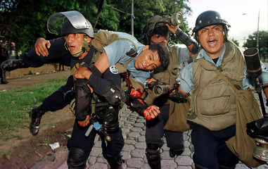 Anti-riot police carry a colleague wounded by a blast from a homemade mortar during clashes with stu..