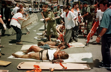 Wounded victims lie in the street waiting to be evacuated to hospital minutes after two bombs ripped..