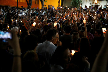 Opposition supporters and students, hold candles during a vigil in homage to victims of violence during the protest against Venezuela's President Nicolas Maduro's government in Caracas