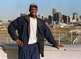 DENVER NUGGETS MCDYESS POSES WITH DENVER SKYLINE BACKGROUND.