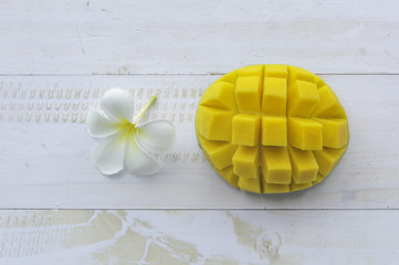 Mango fruit with flower on white wooden background.