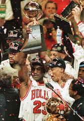 Chicago Bulls Michael Jordan (L) and Scottie Pippen hold the NBA championship trophy following the B..