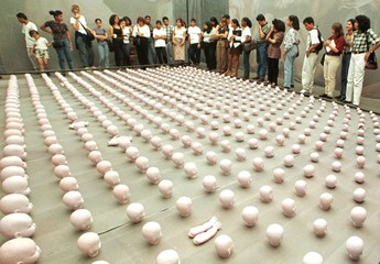Venezuelans marvel at hundreds of tiny, pink, plastic doll heads at an art exhibit placed amongst th..