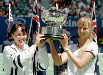 Martina Hingis (L) and Mirjana Lucic hold the women's doubles trophy aloft after winning the final a..