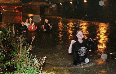 Drivers helped by firemen walk in the water after they left their cars  submerged on the  highway be..