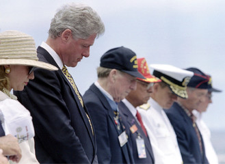 President Clinton and First lady Hillary bow their heads along with veterans on the bow of the aircr..