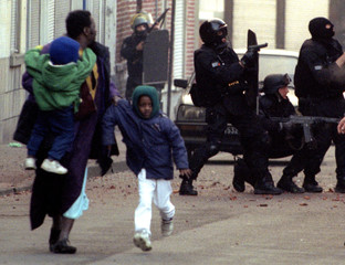 A man holding his children flees the site where French anti-terror police (RAID) attack a house in a..