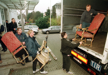 MOVERS CARRY CHAIRS OF THE PRESIDENTIAL OFFICE IN BONN.