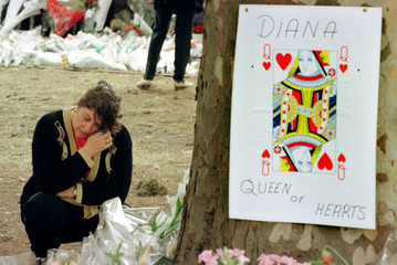 A woman wipes away a tear as she kneels next to a Queen of Hearts card for Diana, Princess of Wales ..