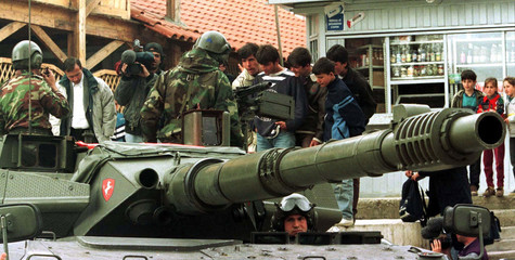 Italian soldiers drive their tank out of the military academy in Tirana whilst being closely watched..