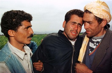SURVIVORS OF TERRORIST ATTACK WEEP AS THEY RETURN TO THE VILLAGE OF MELAS IN ALGERIA.
