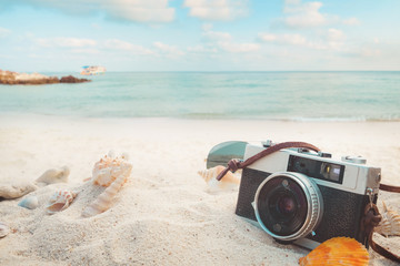 Fototapete - The concept of leisure travel in the summer on a tropical beach seaside. retro camera on the sandbar with starfish, shells, coral on sandbar and blur sea background.  vintage color tone styles.