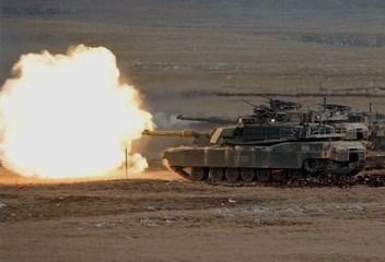 U.S. M-1A Abrams tanks open fire during a live ammunition exercise in Glamoc April 3. A six nation S..