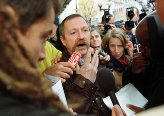 French extrememist protester Jose Bove (C) talks to the media outside a downtown Seattle McDonald's ..