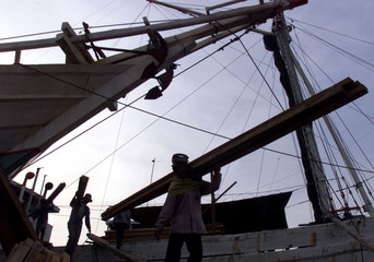 DOCKERS UNLOAD A TRADITIONAL INDONESIAN SAILING BOAT IN JAKARTA.