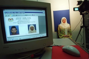 A soon-to-be-married Malaysian woman has her picture taken for the new computerised marriage card in..