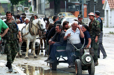 Croatian Serbs (R) who stayed behind in the captured town of Knin, are escorted by Croatian police t..