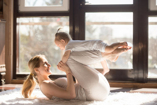 Young sporty mother and baby girl working out, exercising together at home, parent and child healthy development, game playing, fitness and relaxation, wearing white. Healthy lifestyle concept photo