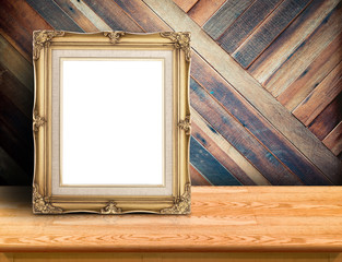 Gold victorian picture frame on plank wooden table top at tropical diagonal wood wall,Template mock up for adding your design and leave space beside frame for adding more content